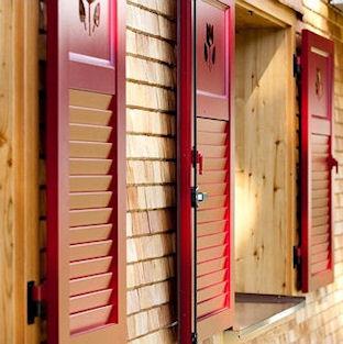 Rote Klappläden aus Aluminium im Holz-Look auf einer Holzfassade