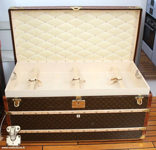 Interior of the Louis Vuitton mail trunk, stencil canvas.   Comprising 3 removable frames with 3 straps. beige canvas interior   Upholstered lid, white ribbon signed Louis Vuitton.