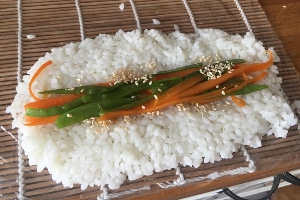 Für ein Inside-Out Sushi: Holzmatte mit Frischhaltefolie umwickeln. Gemüsestreifen rein, etwas Sesam dazu und aufrollen