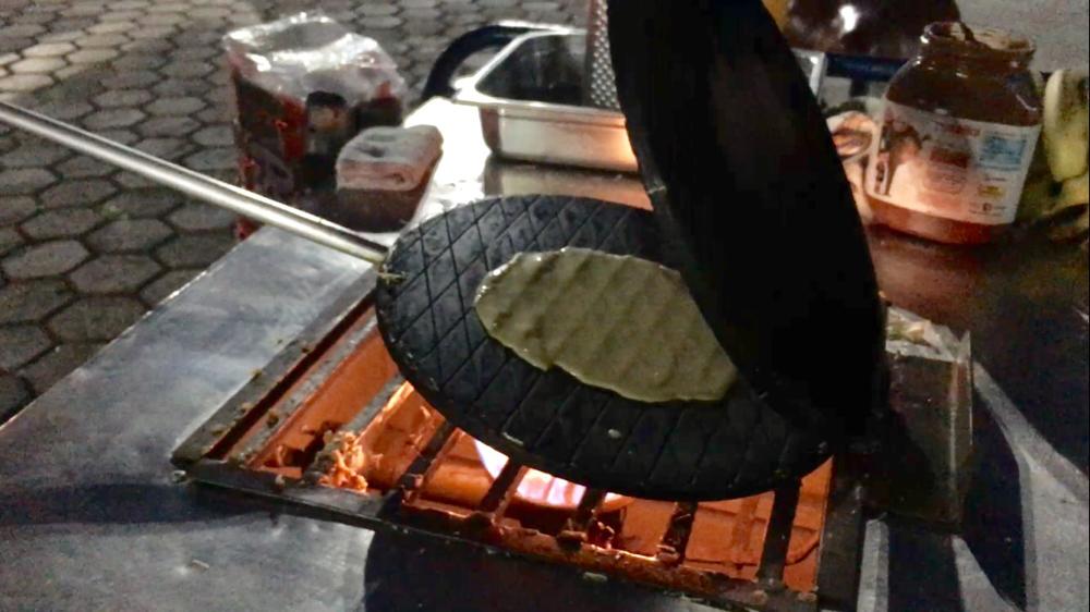 In einem Waffeleisen wird über der offenen Flamme eine ganz dünne, knusprige Waffel gebacken