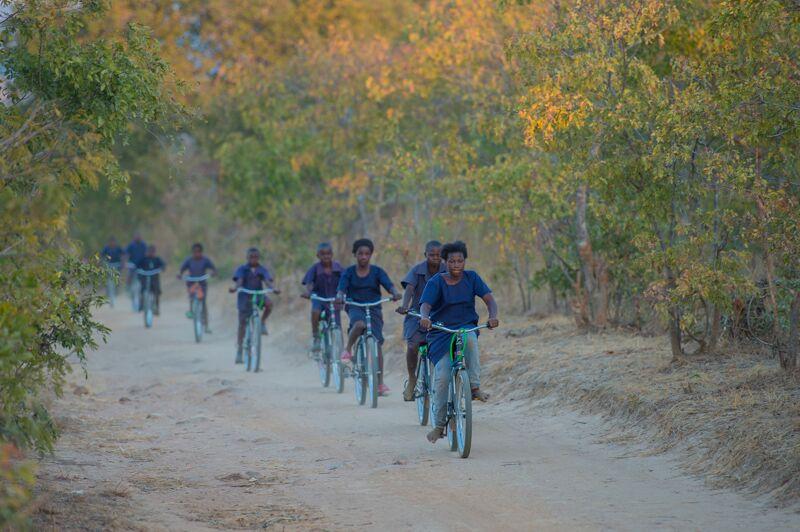 @WorldBicycle Relief/ Im ländlichen Afrika ist der Weg zur Schule oft sehr weit. Zu Fuß kommen die Schüler schon völlig erschöpft in der Schule an. Mit dem Fahrrad brauchen sie nur ein Viertel der Zeit.
