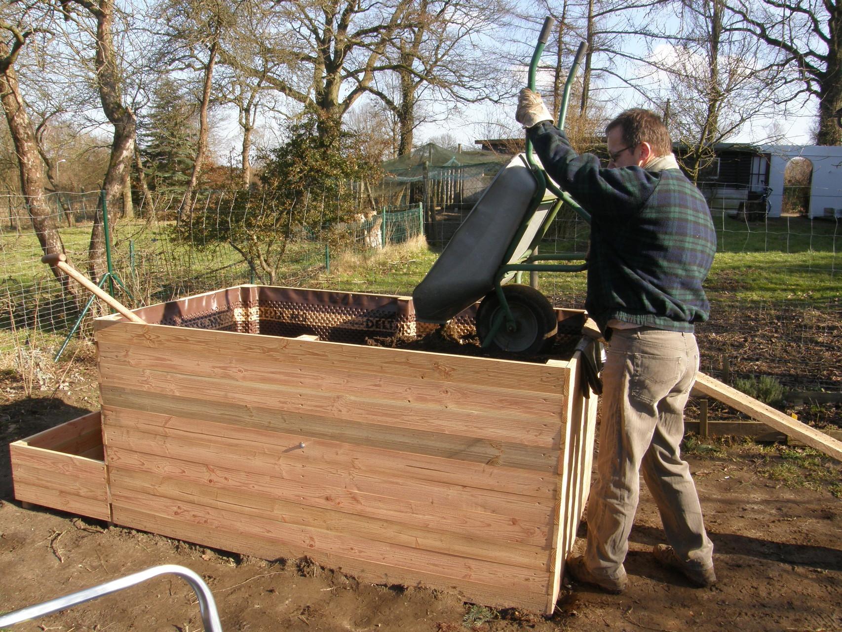 23. Über eine Holzplanke Schubkarren voll halbreifem Kompost einfüllen