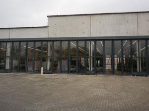 Stahl-Faltflügel-Schnelllauftor - elektrisch oder pneumatisch. Einbau in mitgelieferter Pfosten-Riegelkonstruktion als Abschluss vor  Fahrzeughalle