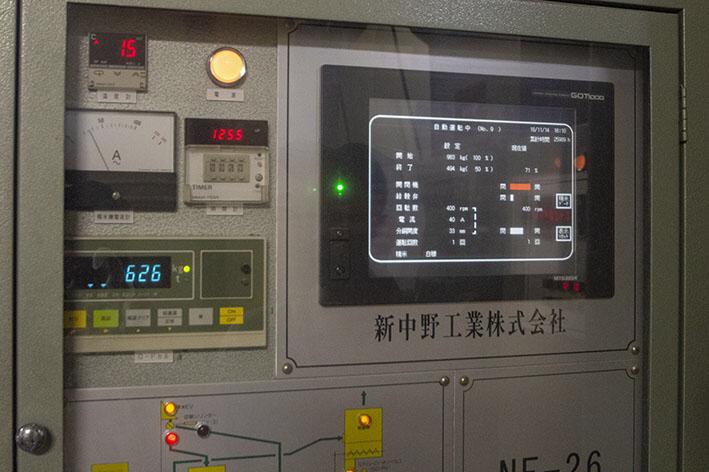 """これが精米屋の """"相棒"""" 、新中野工業社製の醸造用精米機「NF-26FA」。 左側の青い表示「626」は現在の回転数で、1分間に砥石ロールがどれだけ回っているかを示している。なお精米機導入の経緯については、「蔵元インタビュー」第3回をご参照ください。"""