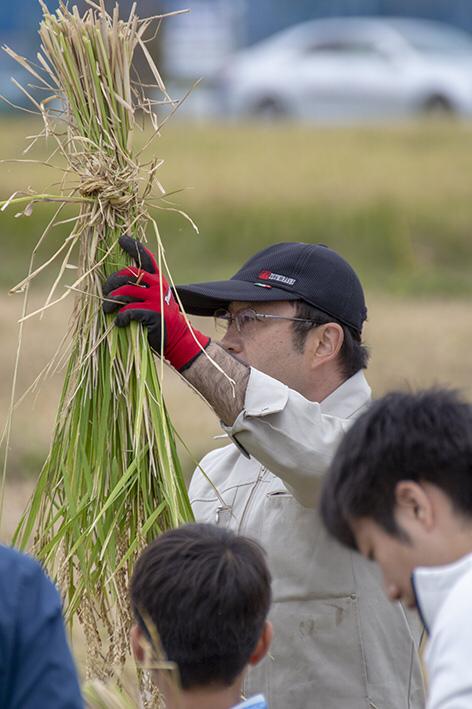 稲の縛り方について説明する高橋靖拡さん