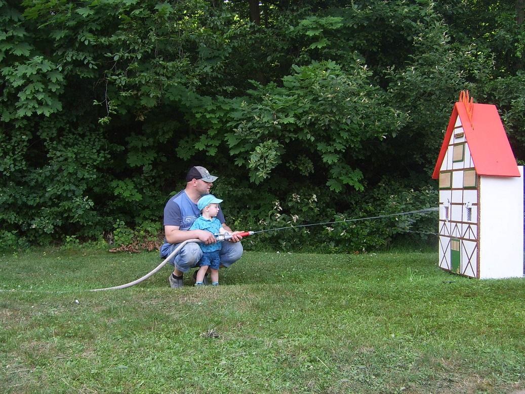 So werden Feuerwehrleute geschmiedet! ;-) Hier der Ortsbandmeister mit seinem Sohn beim Löschen!