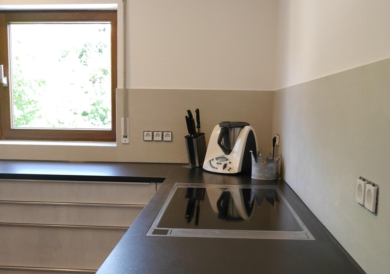 Die großformatigen Fliesen werden als Spritzschutz an Küchenwand verlegt.