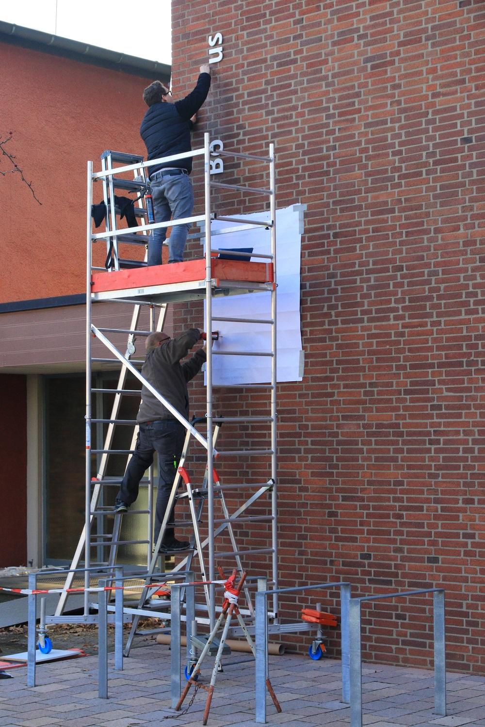 Die Arbeiter beim Anbringen der Beschriftung