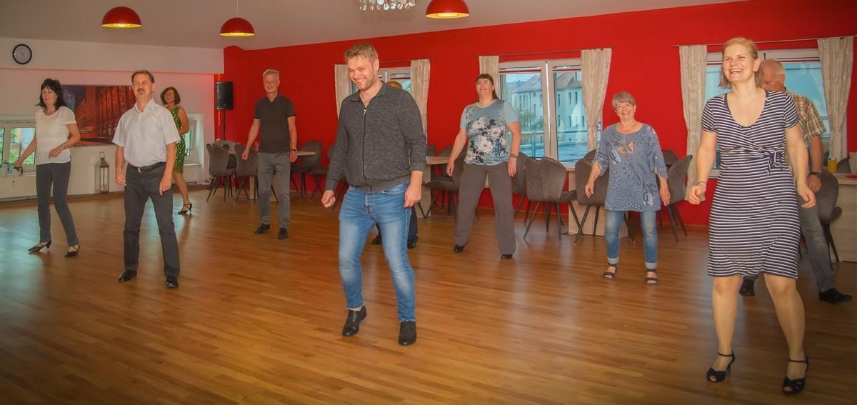 Eine Gruppe von Menschen bewegen sich gezielt um mit ihrem Körper tänzerisch fit zu bleiben
