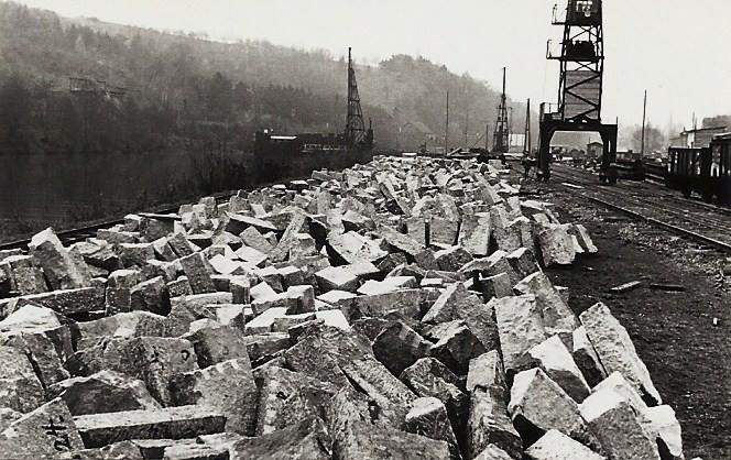 Das Steinlager der Baustelle, rechts einige Regelspurgüterwagen