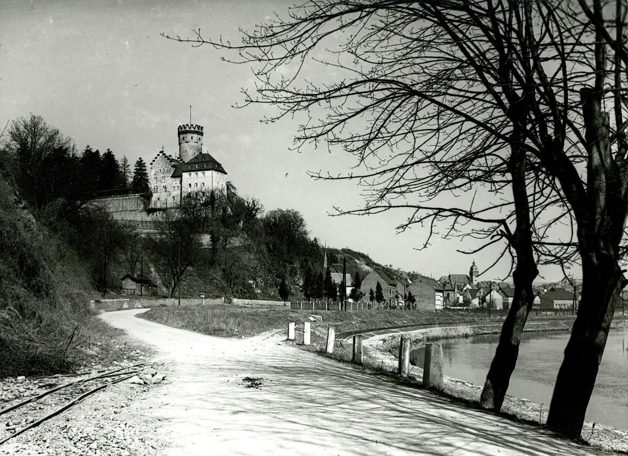 Ortseingang Dehrn, ähnlicher Blickwinkel, die Feldbahn kreuzt die Straße zum Steinbruch