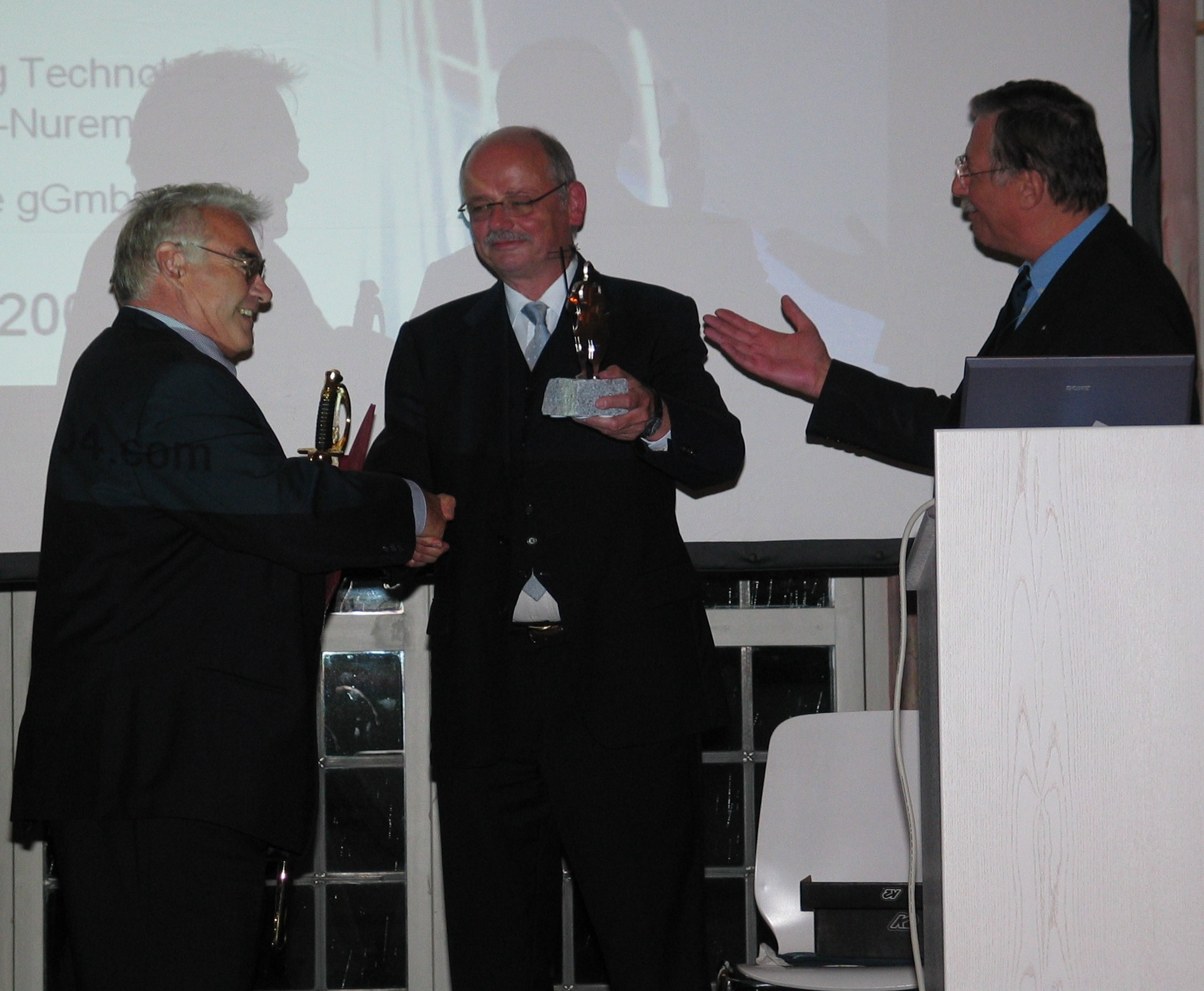 Prof. Jüptner and Prof. Geiger hand over the sword and trophy of the Knights of Laser Technology to Prof. Schuöker at LANE 2004's Conference Banquet (from right to left)