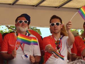 Bild: CSD-Teilnehmer mit Sonnenbrillen und Regenbogenfähnchen