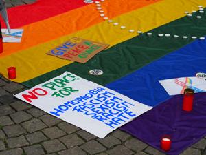 Bild: Plakate, Kerzen und die Regenbogenfahne