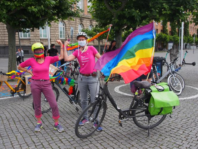 Bild: Fahrradfahrerinnen mit Regenbogenfahne
