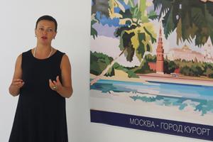 """Bild: Kuratorin Natalia Gershevskaya erläutert das Plakat """"Moscow – city resort"""" von Kostantin Latyshev"""