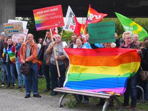 Bild: Demonstrat_innen mit Regenbogenfahnen und Transparenten