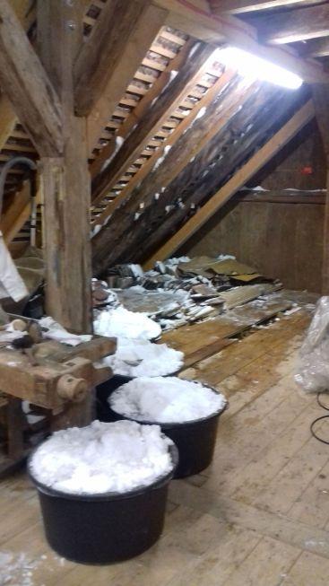 Obwohl nur ein kleiner Teil des Dachbodens bearbeitet werden konnte, sammeln sich in den herbeigeschafften Behältern beachtliche Schneemengen an.