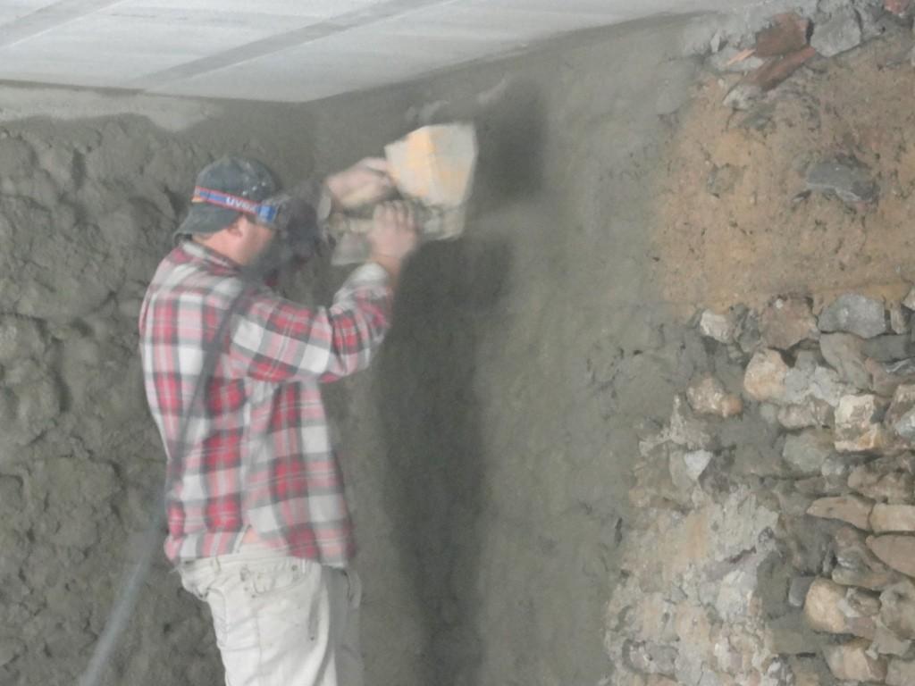 2009 : On projette du ciment contre les murs avant de commencer l'isolation