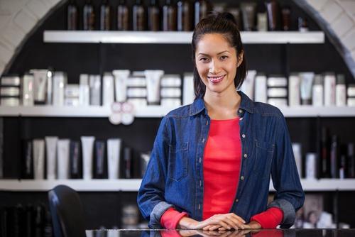 femme souriante devant un présentoir de produits de beauté