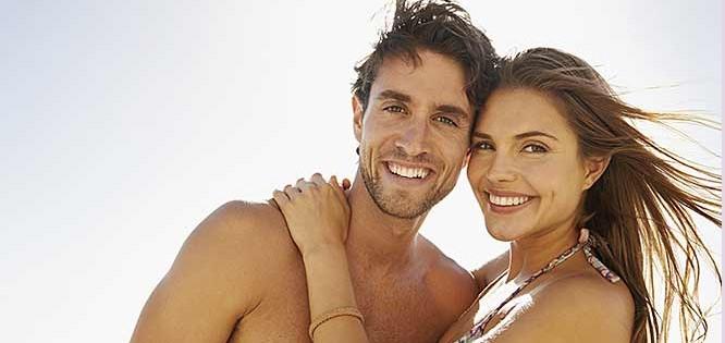 lachendes Pärchen - ein Mann und eine Frau - leicht bekleidet im Sommerurlaub mit wehenden Haaren