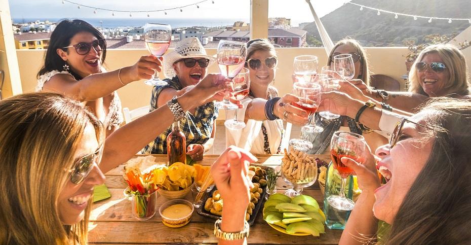 Eine Gruppe von Frauen unterwegs in Europa stoßen mit Gläsern an und feiern. Gut abgesichert mit einer günstigen Gruppen-Reiserücktritts-Versicherung der ERGO Reiseversicherung