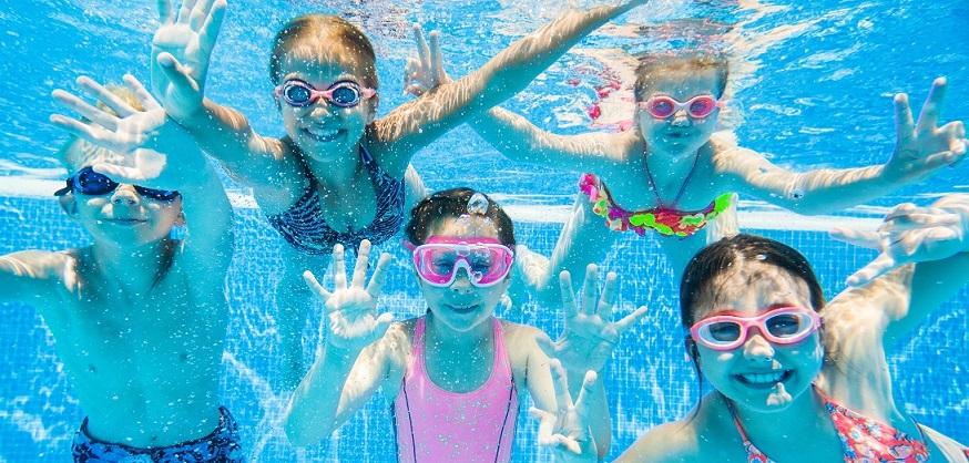 Eine Gruppe von Kindern schwimmt im Pool mit bunten Tauchermasken. Gut abgesichert mit einer günstigen Schüler-Reiserücktritts- und Reisekranken-Versicherung der ERGO Reiseversicherung