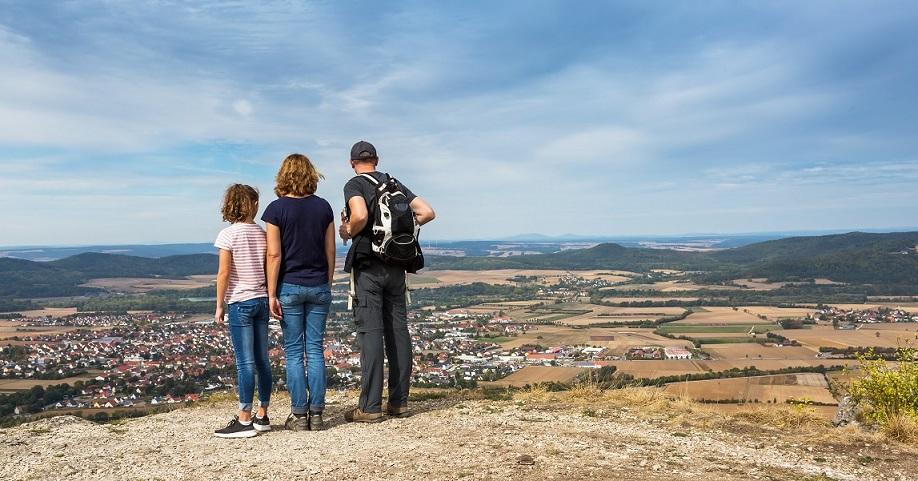 Eine Frau, ein Mann und ein Kind stehen auf einem Berg und schauen im Urlaub in die Landschaft, gut versichert mit einer ERGO Jahres-Reiseversicherung für mehrere Reisen im Jahr mit Coronaschutz