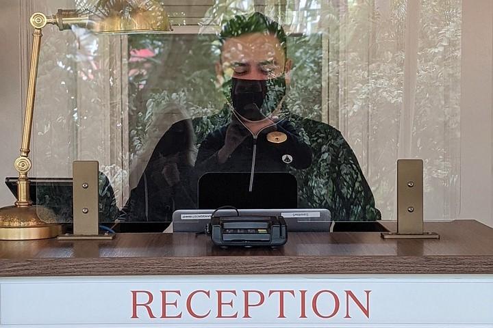 Ein Mann mit Maske steht hinter der Hotelrezeption mit Plexiglas als Synonym für die Initiative #perspektivejetzt