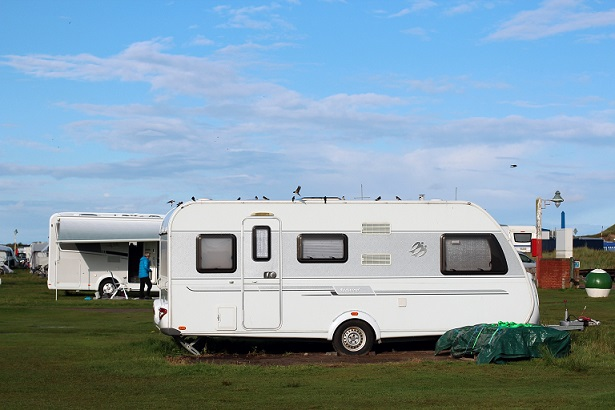 Caravan Wohnmobile stehen auf einem Reisemobil-Stellplatz. Hoffentlich CDW versichert mit der Camping-Versicherung der ERGO.