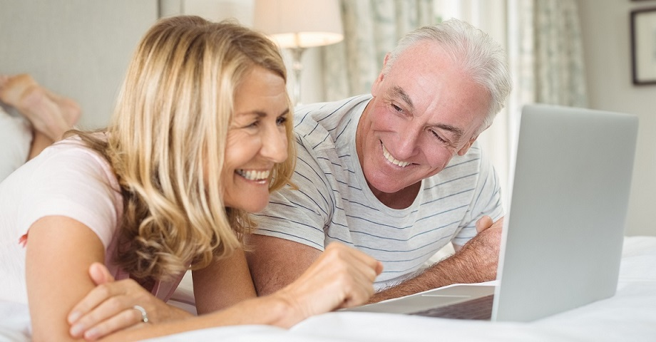 Eine Frau und ein Mann liegen mit einem Laptop auf dem Bett und buchen online eine Reiseversicherung für einen Urlaub in Deutschland
