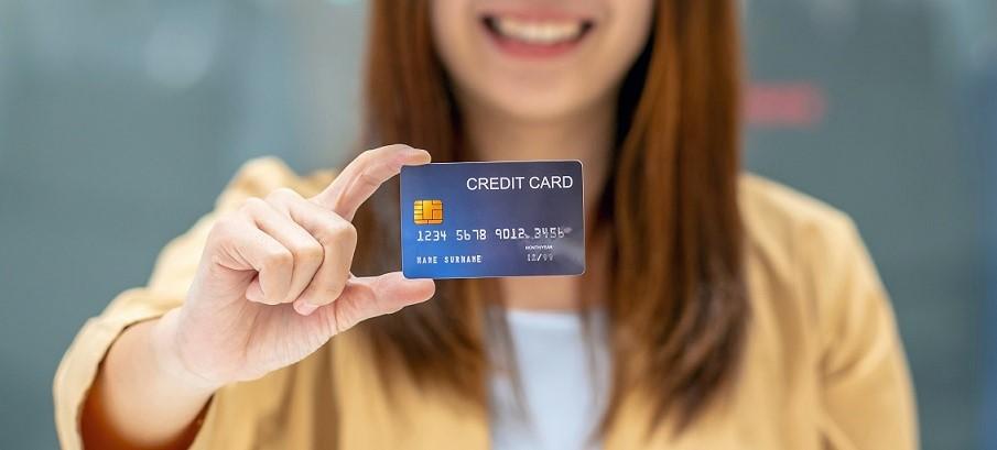 Eine Frau hält ihre Kreditkarte hoch. Sie weiß nicht, welche Reiseversicherungen darin enthalten sind.