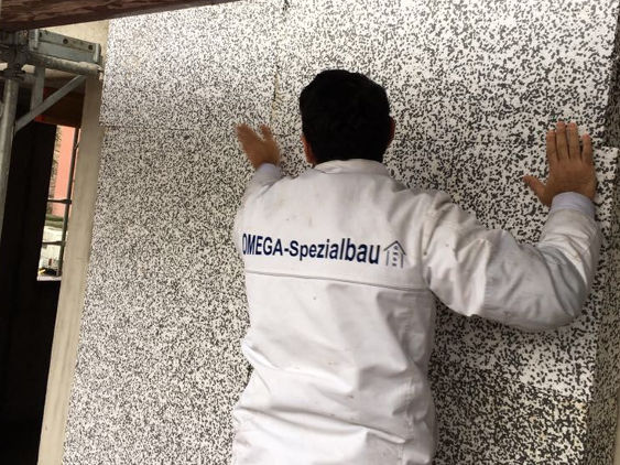 Ein Mitarbeiter der Omega-Spezialbau GmbH beim dämmen einer Außenfassade