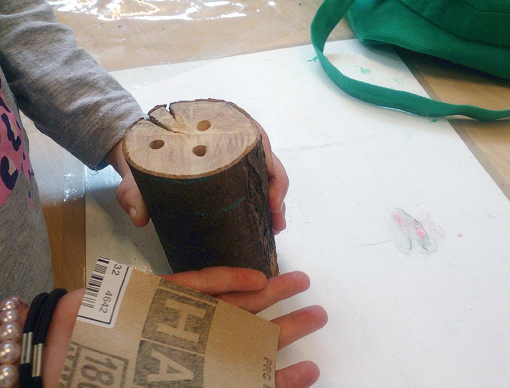 """Ein kleiner Baumstamm ist mit Bohrlöchern versehen.  Zimmer im """"Insektenhotel"""" entstehen."""