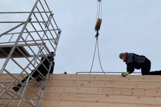 Handwerker bei der Arbeit - Hausbau - Holzbau - Blockhausbau -Blockhaus Baustelle - Montage - Bayern