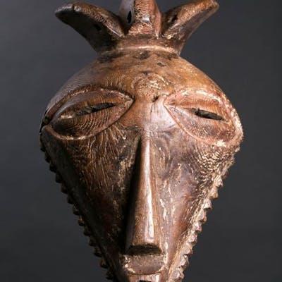 Maschera Basikasingo caratterizzata dal viso a tetraedo, i grandi occhi globulari e la barba che ne circonda il profilo inferiore