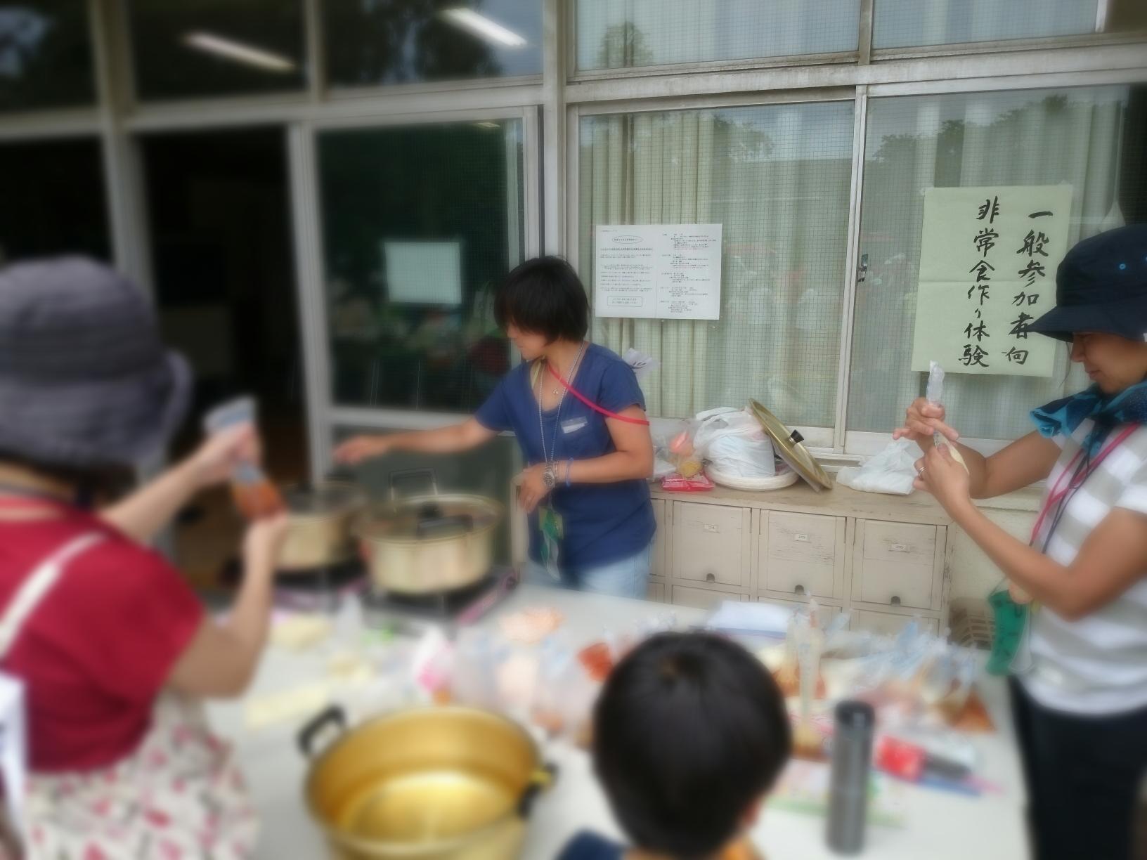 非常食作り紹介 PTAさんがお鍋の水を沸かして、ハイゼックス袋にいれたご飯などの調理と試食コーナー
