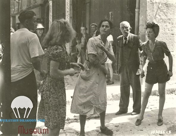 la fameuse photo du National Archives USA, la jeune fille de dos qui avait entretenue des relations avec l'occupant, en robe claire, Lili RAYNAUD, à droite sa fille Rosette qui viens d''être délivrée des locaux de la Gestapo par les Libérateurs.