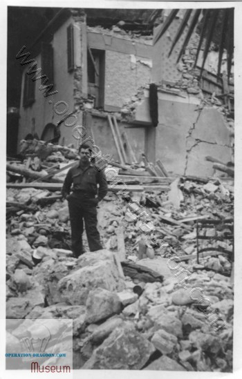 Robert Cooper standing in the rubble of the inn that a time-bomb blew up, Nov. 4, 1944.