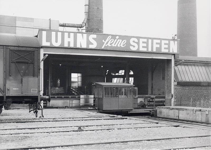 Ein Werkfoto der Firma Luhns aus der  Sammlung VOBA aus ähnlicher Perspektive. Der gedeckte Güterwagen steht im Abholgleis des Anschlusses. Das Foto stammt aus Mitte der 1970er Jahre.