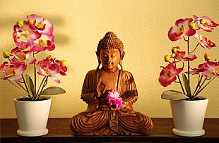 Traditionelle Buddha Holzfigur mit Orchideen Pflanzen