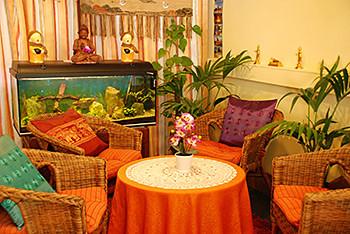 Gemütlicher Wartebereich mit Aquarium und Rattansesseln bei Tabandu Thai Massage in Mainz