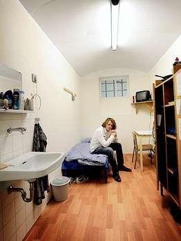 Der Reporter in einer Musterzelle mit schmalem Bett, Schrank, Waschbecken und Fernseher_JVA Mannheim