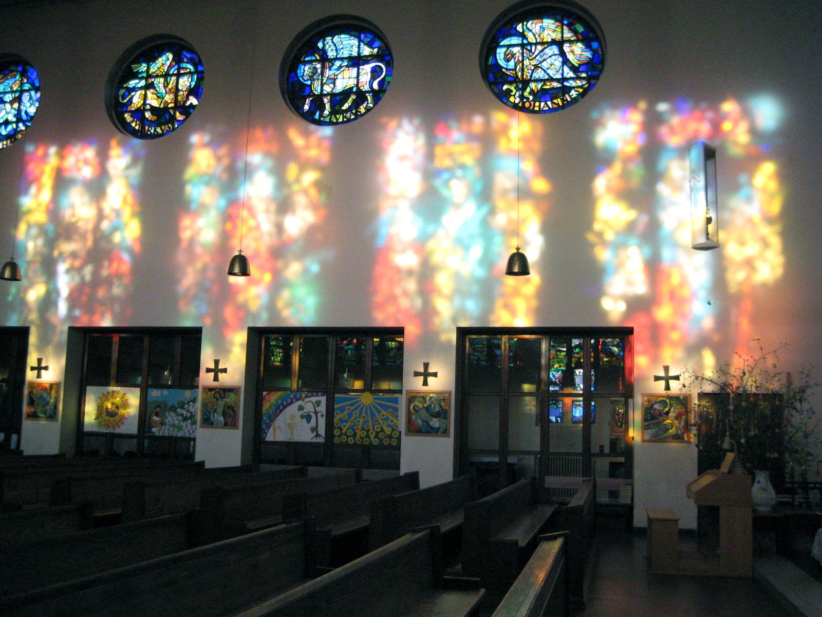Vier runde Mosaikfenster von Karl Hauk in der Westwand mit den Symbolen der 4 Evangelisten