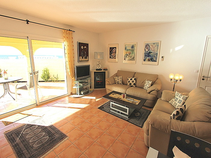 Wohnbereich mit E - Kamin und Blick auf dir untere Terrasse.