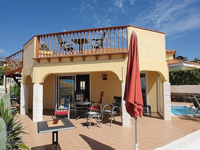 Ansicht der Ferien - Villa mit Pool und Meerblick vom Garten mit Terrasse .