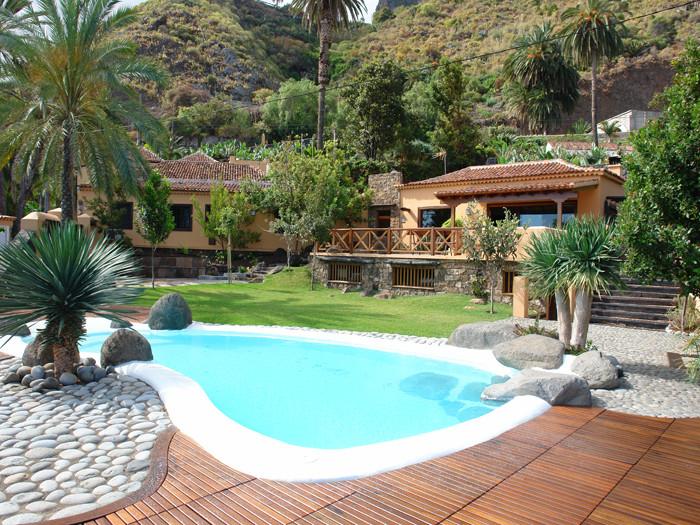 Im Vordergrund vom Bild ist der Pool zu sehen, dann kommen die Ferienhäuser und die Berge sieht man im Hintergrund.