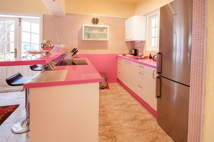 Die großzügige Küche ist mit  kleinen Mosaikfliesen gefliest und die Einbauküche ist in rosse gehalten.