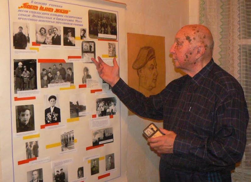 """И.М. Бондаренко возле стенда с фотографиями """"Такая долгая жизнь"""""""