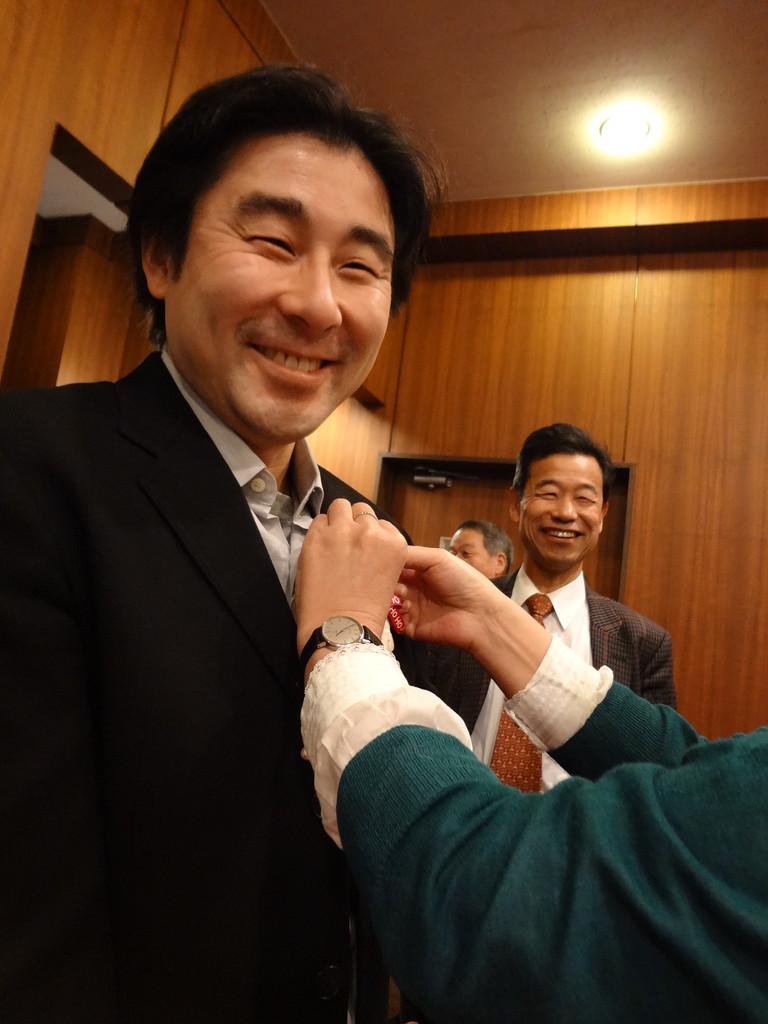 団員作成のクリスマスブローチをつけてもらう山口先生